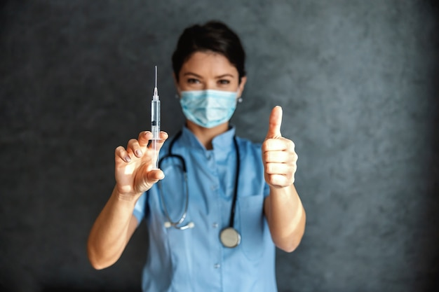 Doctor con máscara en la cara sosteniendo la vacuna covid-19 y empujando los pulgares hacia arriba