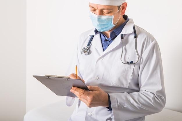 Doctor en máscara con el estetoscopio que escribe la prescripción de rx en el tablero en el fondo blanco, primer. servicio médico