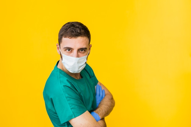Doctor en máscara médica con brazos cruzados.