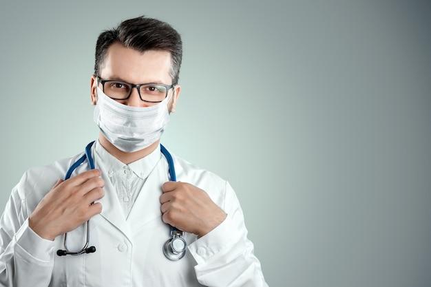 Doctor en una máscara médica en una pared de luz. el concepto de prohibición de salir de casa, autoaislamiento, cuarentena, precauciones, distancia, covid-19.