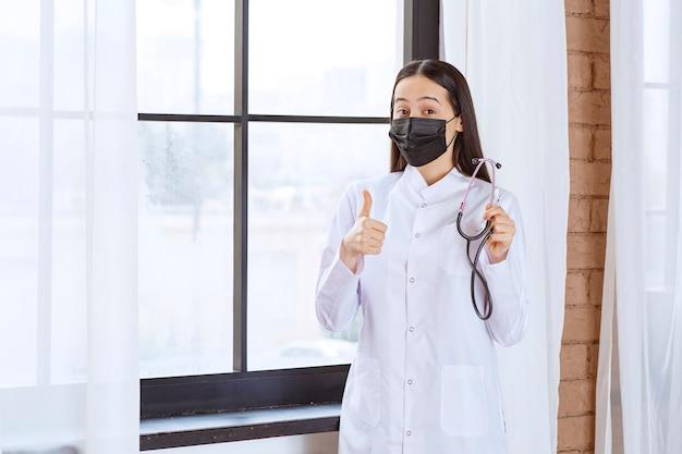 Doctor en máscara negra con un estetoscopio de pie junto a la ventana y mostrando el signo de satisfacción.