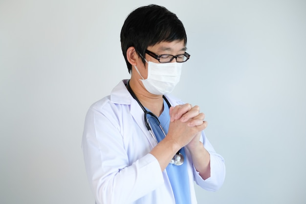 Doctor con máscara protectora rezando