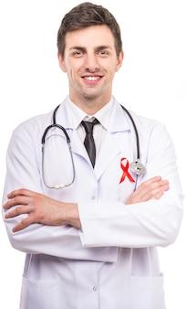Doctor masculino hermoso con la cinta roja como símbolo del sida.