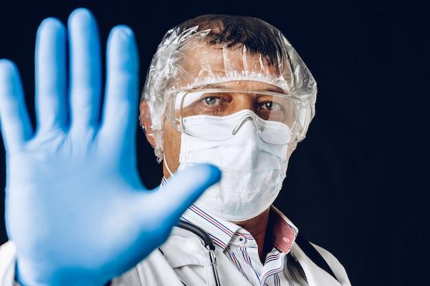 Doctor masculino mostrando señal de stop. doctor vistiendo guantes y mascarilla médica. de cerca.