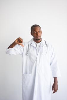 Doctor masculino negro serio que muestra el pulgar hacia abajo. daño al concepto de salud.