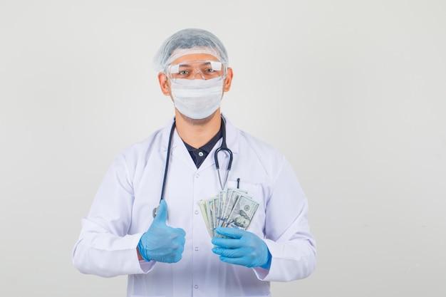 Doctor masculino en ropa protectora con billetes de dólar, inventando el pulgar