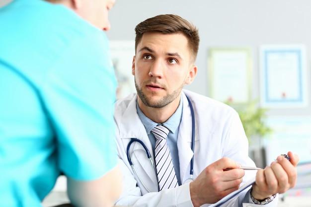 Doctor masculino serio que pide consejo a un colega sobre un caso médico difícil