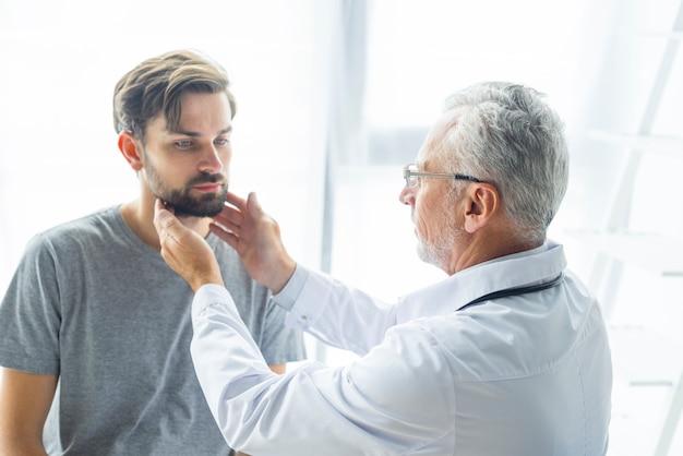 Doctor mayor que examina los nodos de linfa del paciente