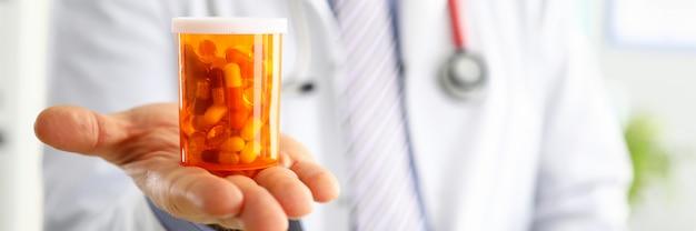 Doctor en medicina masculina mano sosteniendo y ofreciendo al paciente tarro de pastillas. concepto de seguro de farmacología de prescripción de atención médica. dar o mostrar medicamentos al paciente. médico listo para ayudar