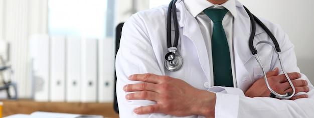 Doctor en medicina masculina manos cruzadas sobre su pecho en la oficina