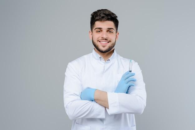 Doctor en medicina sonriente en guantes con suringe aislado sobre fondo gris