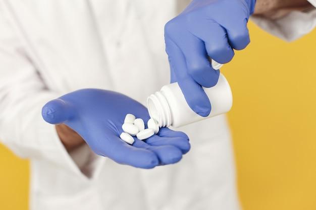 Doctor en medicina sonriente con pastillas. aislado. hombre en guantes azules.