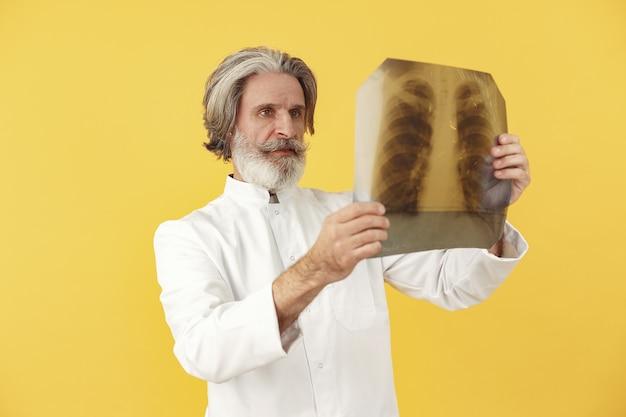Doctor en medicina sonriente con resultados de rayos x. aislado.