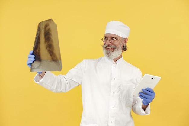 Doctor en medicina sonriente con tableta. aislado. hombre en guantes azules.