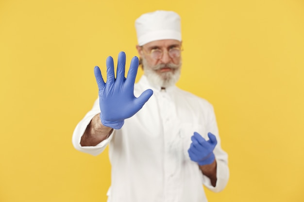 Doctor en medicina sonriente en vasos. aislado. hombre en guantes azules.