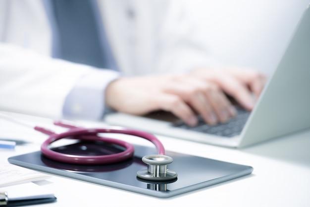 Doctor en medicina trabajando en la computadora en la sala de examen