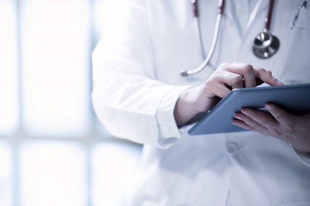 Doctor en medicina usando tableta inteligente para trabajar en el hospital