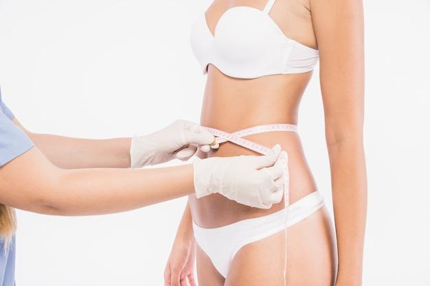 Doctor medir la cintura de la mujer
