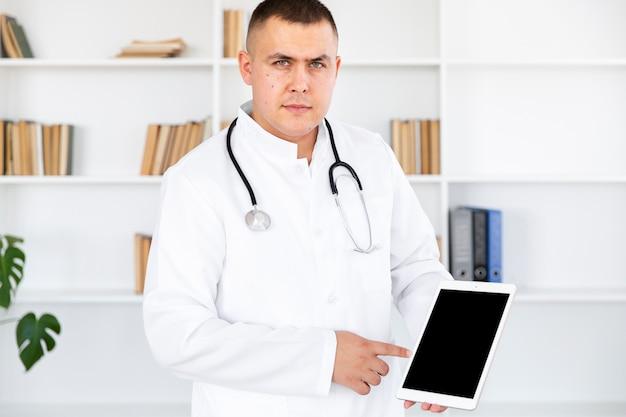 Doctor mirando al fotógrafo y sosteniendo una foto simulada