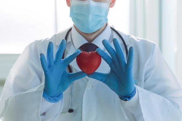 El doctor está mirando el corazón en sus manos