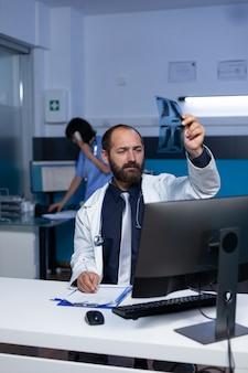 Doctor mirando escaneo de rayos x en la mano para diagnóstico médico