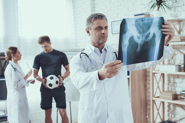 El doctor está mirando la radiografía para el atleta