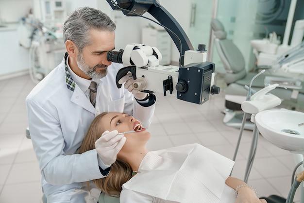 Doctor mirando a través del microscopio dental los dientes de la mujer.