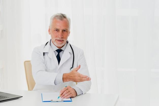 Doctor mostrando al paciente dónde sentarse