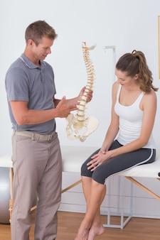 Doctor mostrando la columna vertebral anatómica a su paciente