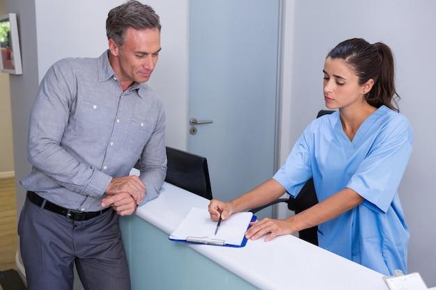 Doctor mostrando documento al hombre en el escritorio