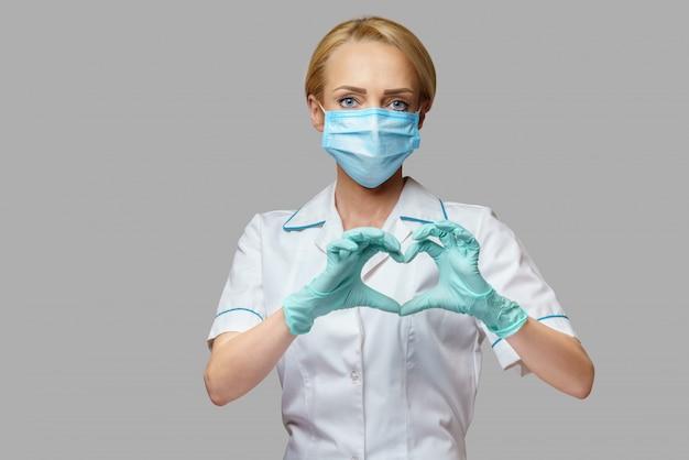 Doctor mostrando forma de corazón por sus manos en guantes estériles