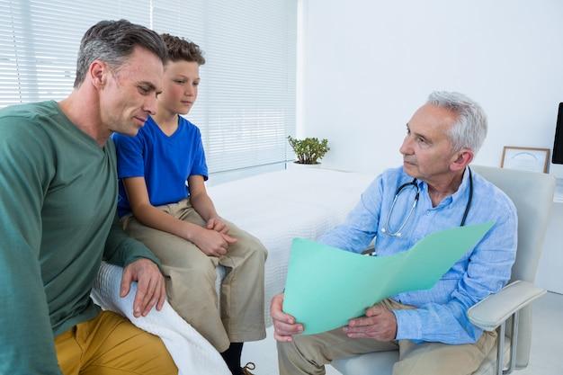 Doctor mostrando informe médico al paciente y sus padres