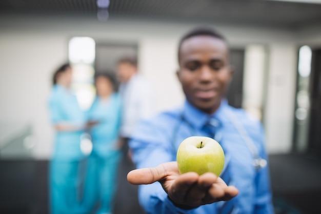 Doctor mostrando manzana verde en el pasillo del hospital