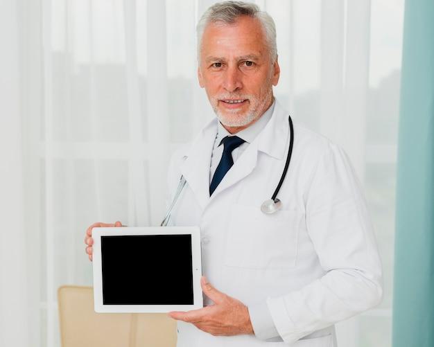 Doctor mostrando maqueta de pantalla de tableta