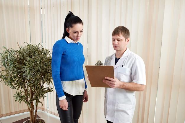 Doctor mostrando paciente femenino sus resultados de pruebas médicas en corredor