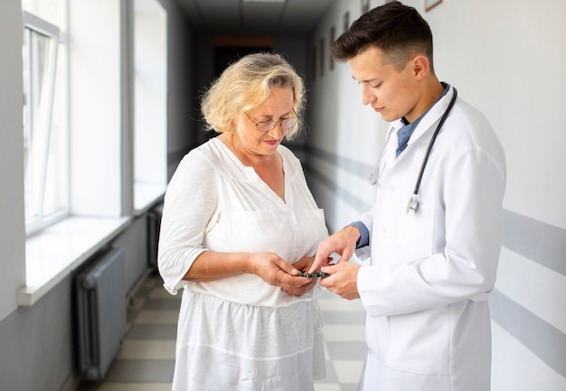 Doctor mostrando píldoras pacientes para tratamiento