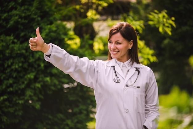 Doctor mostrando los pulgares para arriba al aire libre