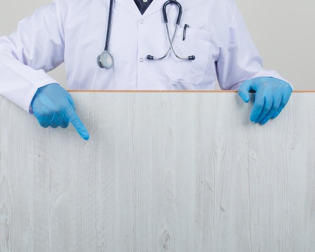 Doctor mostrando tablero de madera en bata blanca y guantes