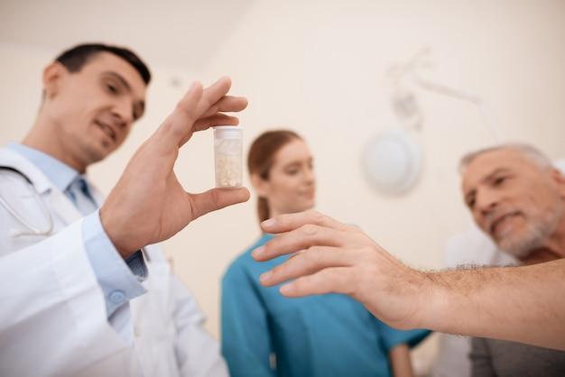 El doctor le muestra al anciano una pastilla que necesita tomar