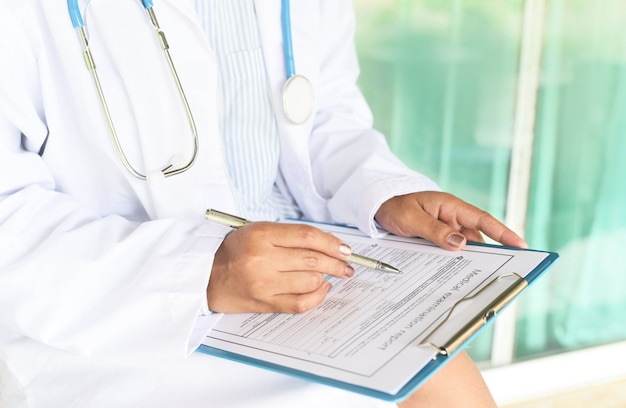 Doctor mujer asiática nota sobre historia clínica. informe de examen médico para diagnóstico en el hospital.