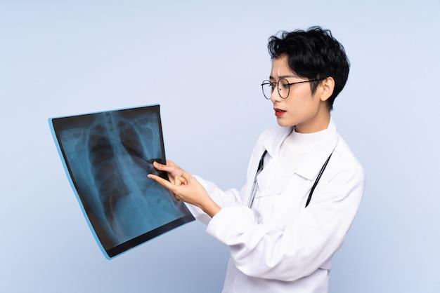 Doctor mujer asiática sosteniendo una exploración ósea sobre pared azul aislada