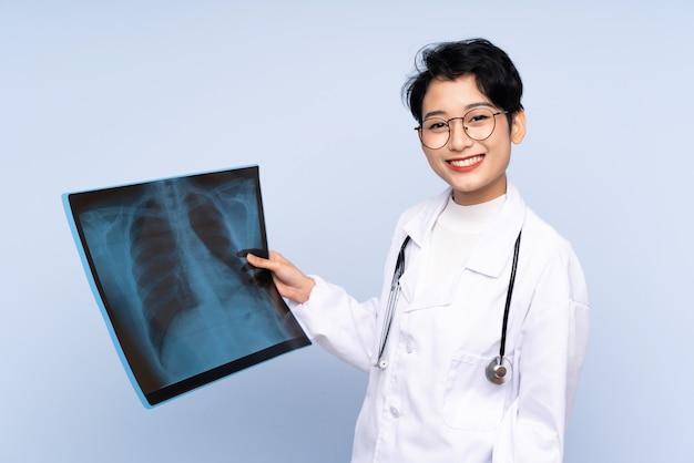 Doctor mujer asiática sosteniendo una gammagrafía ósea