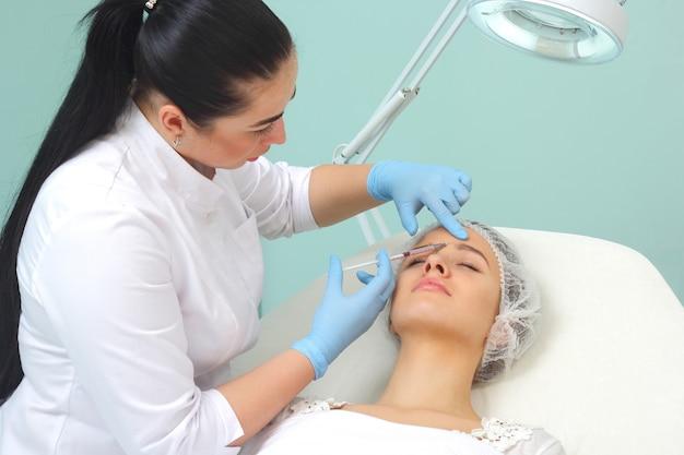 Doctor mujer dando inyecciones de botox.