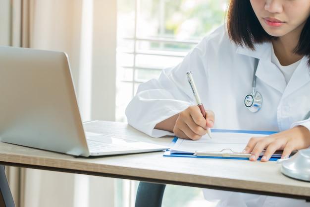 Doctor de la mujer escribiendo portapapeles de prescripción con registro de papel de información