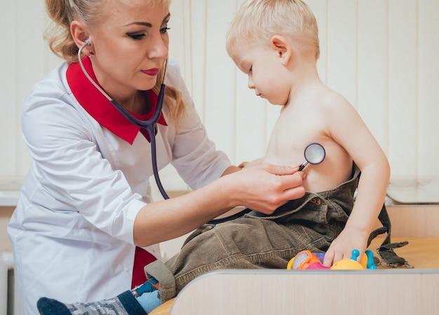 Doctor mujer examinando los latidos del corazón del niño con estetoscopio