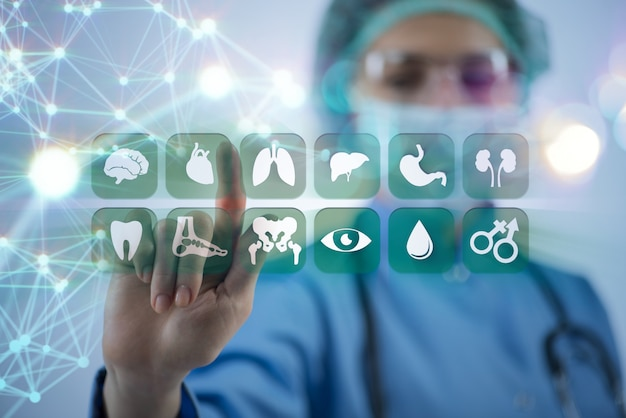 Doctor de la mujer que presiona los botones con varios iconos médicos
