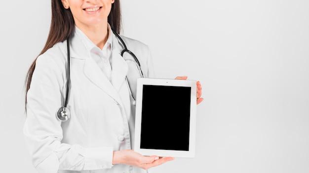 Doctor mujer sonriendo y sosteniendo la tableta