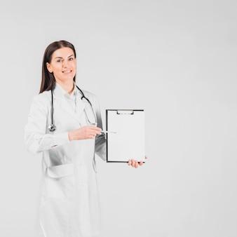 Doctor mujer sonriente y mostrando en el portapapeles
