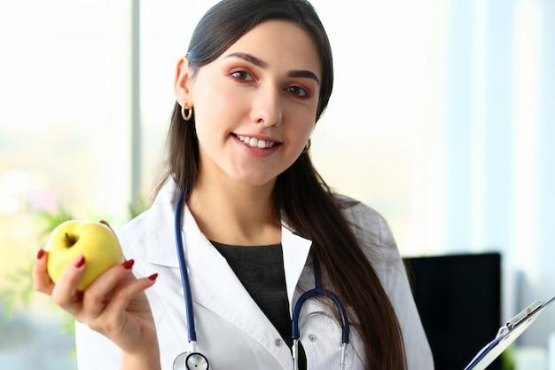 Doctor mujer sosteniendo manzana verde