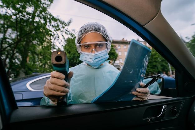 Doctor mujer usa pistola termómetro infrarrojo para verificar la temperatura corporal